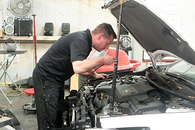 Riggs works on a car engine