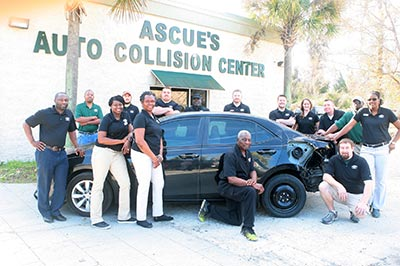 Ascue's Auto Collision Center Staff posing by a wrecked car